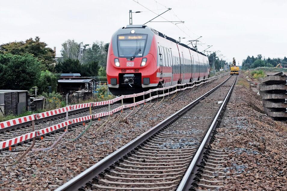 Während auf dem einen Gleis gearbeitet wird, fährt auf dem anderen Gleis ein Zug.