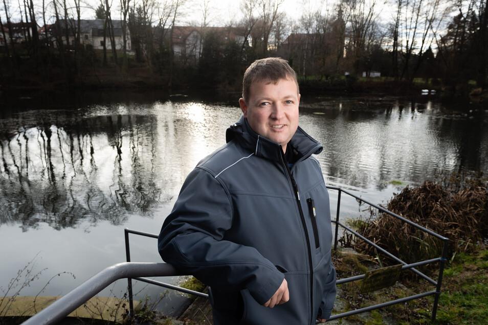 """René Schubert vom Schmöllner Verein der Heimatfreunde steht am Mühlteich. """"Hier liegt der Ursprung unseres Dorfes"""", sagt er. Der Heimatverein setzt sich dafür ein, dass der Teich saniert wird und warb dafür gegenüber der Gemeinde."""