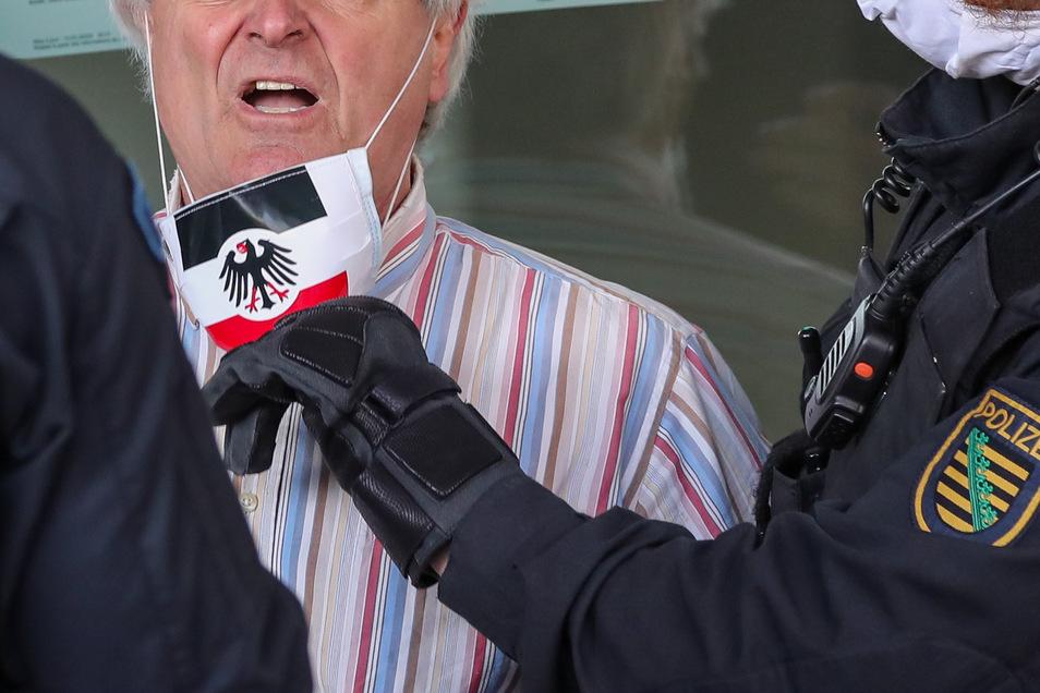 Wie hier ein mit Mundschutz in den Farben der Reichskriegsflagge und dem Bundesadler ausgestatteter Teilnehmer auf einer Kundgebung in Chemnitz, kommen im Landkreis Görlitz Reichsbürger ebenso mit dem Gesetz in Konflikt. Auch in Corona-Zeiten.