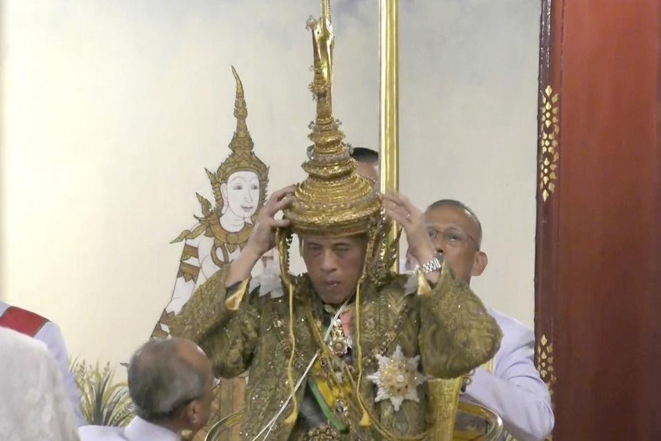 Thailands König Maha Vajiralongkorn setzt sich bei der feierlichen Zeremonie seiner Krönung in Bangkok selber die Krone auf,