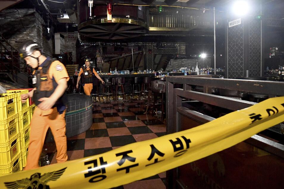 In einem Nachtclub ist ein Innenbalkon eingestürzt, Rettungskräfte arbeiten hinter einem Absperrband.