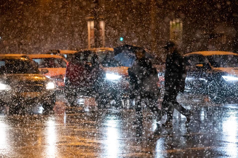 Passanten und Autofahrer kämpfen sich bei Schneefall durch Nürnberg.