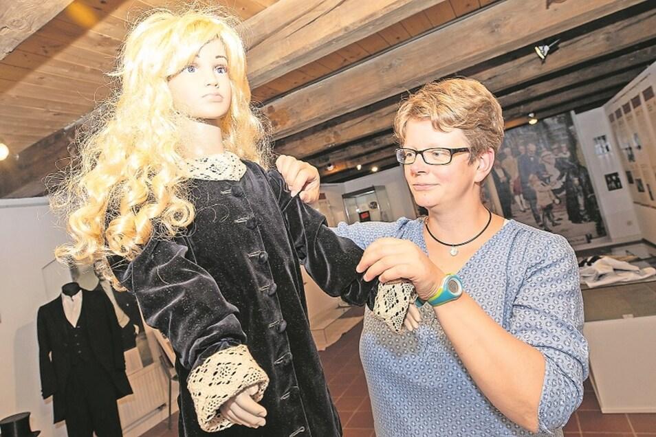 """Museumsleiterin Ulrike Hentzsche kleidet eine Puppe mit einem Originaloberteil des """"Fauntleroy-Styles"""" aus dem 18. Jahrhundert ein."""