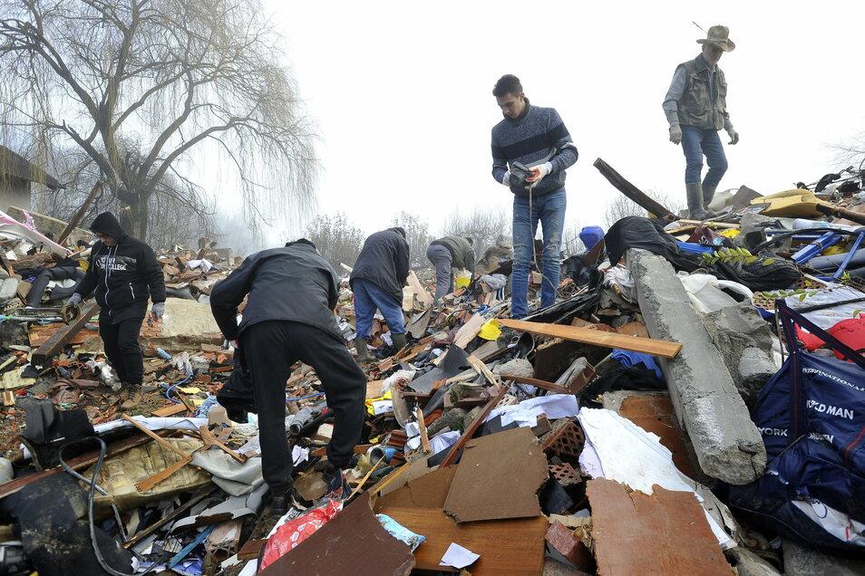 Kroatien, Poljana: Menschen durchsuchen die Trümmer von eingestürzten Häusern.