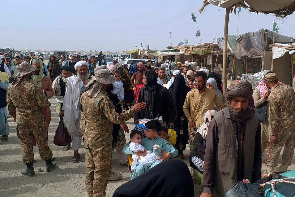 Pakistanische Soldaten überprüfen die Papiere von Menschen, die die Grenze zu Afghanistan an einem Grenzübergang überqueren. Experten rechnen angesichts der Situation in Afghanistan mit vielen Flüchtlingen.