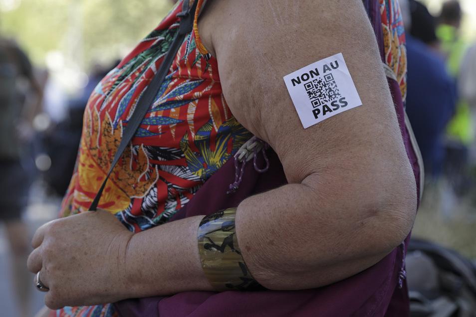 Eine Frau mit einem Aufkleber gegen den Gesundheitspass auf dem Arm demonstriert in Paris gegen die Corona-Regeln.
