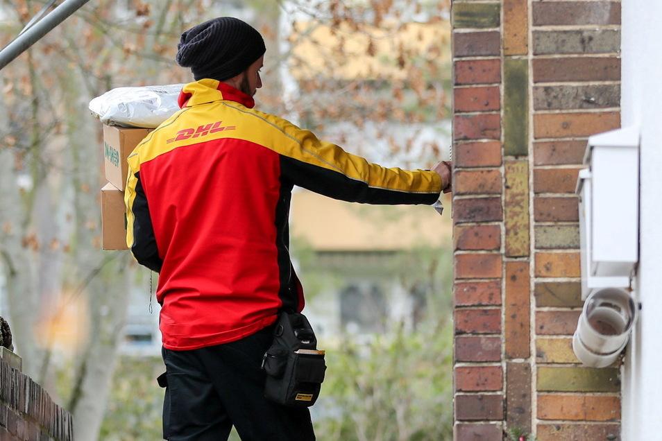 Ein DHL-Paketzusteller steht mit mehreren Sendungen an einem Haus. Oft übergeben die Paketboten die Sendungen nicht persönlich, das sorgt für Ärger bei Empfängern.