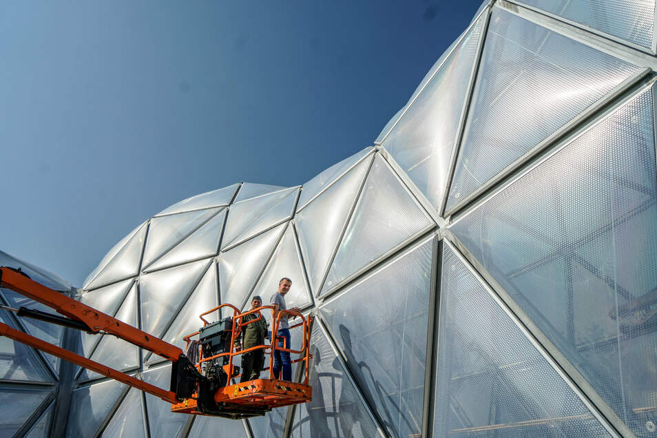 Mitarbeiter einer Spezialfirma kontrollieren die Außenhaut vom Mitoseum, das den Eingang des Saurierparks in Kleinwelka bildet.