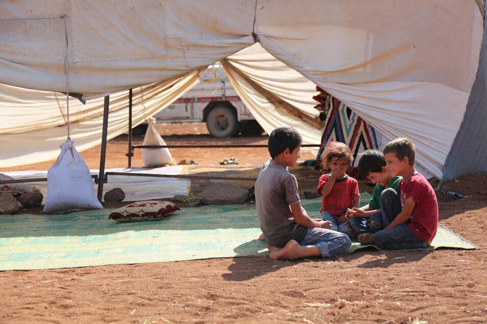 Kinder sitzen vor ihrem Zelt in einem provisorischen Flüchtlingslager.