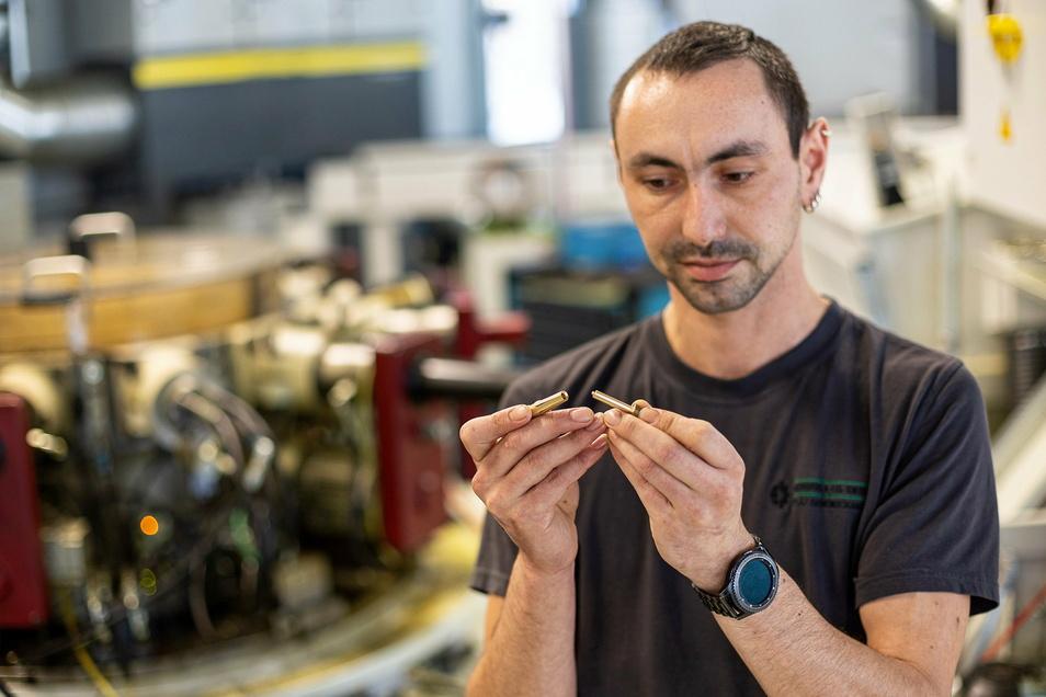 Mitarbeite Rico Thrun zeigt hier Stecker und Buchse, die bei Herbrig gedreht und später zum Laden eines Elektroautos eingesetzt werden.