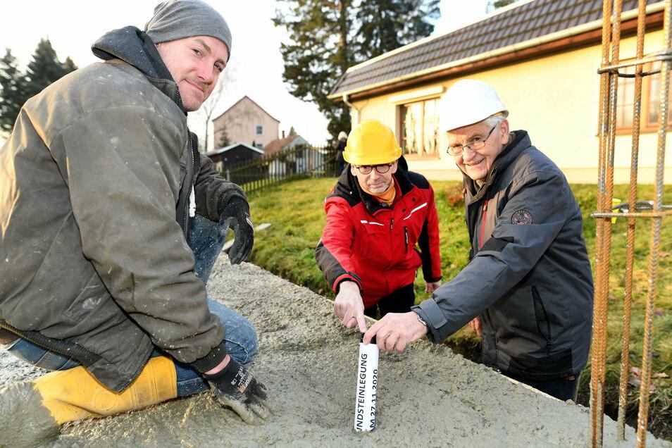 Leutersdorfs Bürgermeister Bruno Scholze (rechts) versenkt mit Vertretern von Baufirma und Planungsbüro bei der Grundsteinlegung für den neuen Kindergarten eine Zeitkapsel in der Bodenplatte.