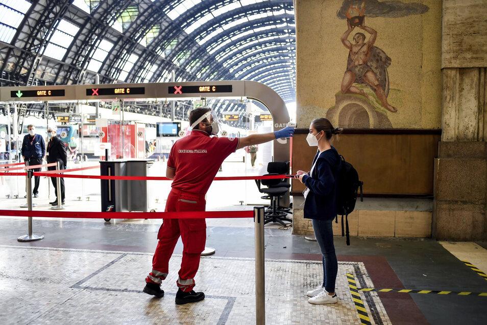 Italien, Mailand: Eine Reisende (r) wird am Hauptbahnhof auf ihre Körpertemperatur überprüft. In Italien herrscht nach rund drei Monaten mit Corona-Beschränkungen wieder weitgehende Reisefreiheit.