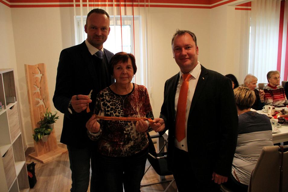 Sven Viehrig (links) und Tino Hütter übergeben den Schlüssel für die Begegnungsstätte der WGF in Hartha an Karin Cvancara.