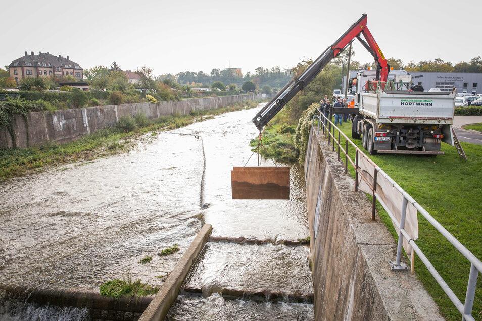 Die bis 2012 errichtete Fischaufstiegsanlage konnte jetzt erst geöffnet werden, da die Weißeritz flussaufwärts bis zu diesem Jahr ausgebaut wurde. Am Donnerstag schwebte diese Stahlplatte am Kranarm empor, die die Fischtreppe bisher verschlossen hatte.