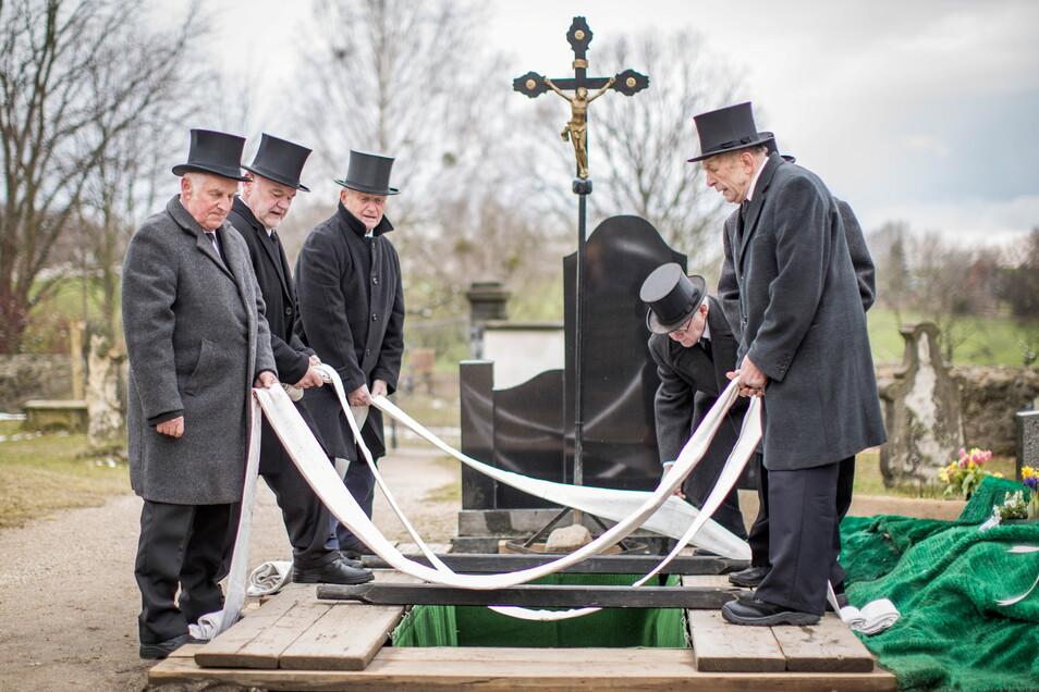 """""""Man tut ein gutes Werk"""": Vor der Beisetzung bereiten die Sargträger die Grabstelle vor und legen die Senkbänder bereit."""