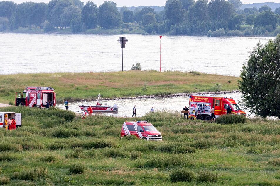 Einsatzkräfte der Polizei, Feuerwehr und DRLG arbeiten am Ufer des Rheins.