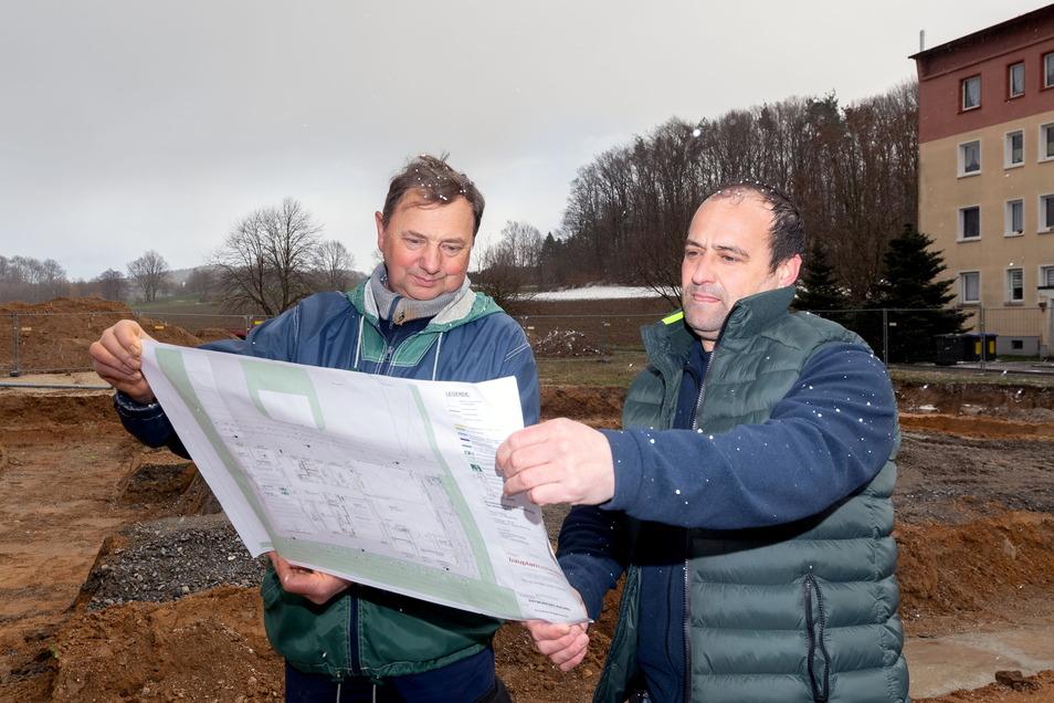 Ortswehrleiter Gerolf Marschner (r.) und sein Stellvertreter Thomas Aust schauen sich die Baupläne des neuen Feuerwehrgerätehauses im Bischofswerdaer Ortsteil Großdrebnitz an. Die Arbeiten haben kürzlich begonnen.
