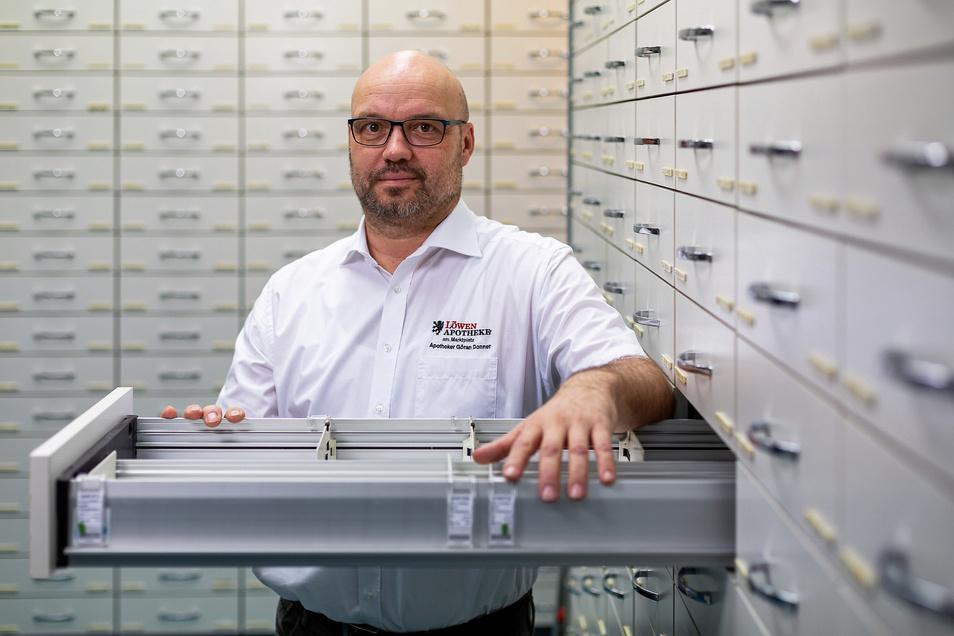 """Apotheker Göran Donner vor einem leeren Fach im Medikamentenregal. """"Das größte Problem ist die Verunsicherung."""""""