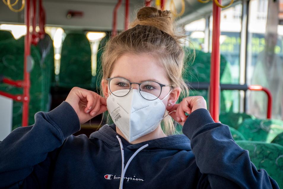 Ein Kind mit viel zu großer FFP2 Maske im Bus.