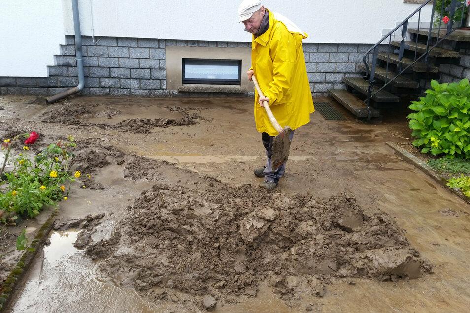 Alle verfügbaren Mitarbeiter des Oderwitzer Bauhofs - hier im Bild Volker Weber - helfen den betroffenen Anwohnern bei der Schlammberäumung.