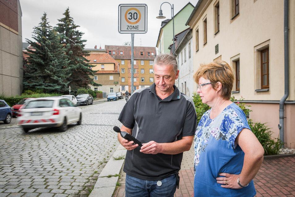 Anwohner protestieren gegen den Straßenlärm und die schlechte Fahrbahn auf der Stolpener Straße in Radeberg. Andreas Krohn hat ein Lärmmessgerät mitgebracht. Carola Nietzsche sieht sich das Ergebnis an. Mehr als 80 Dezibel werden angezeigt.