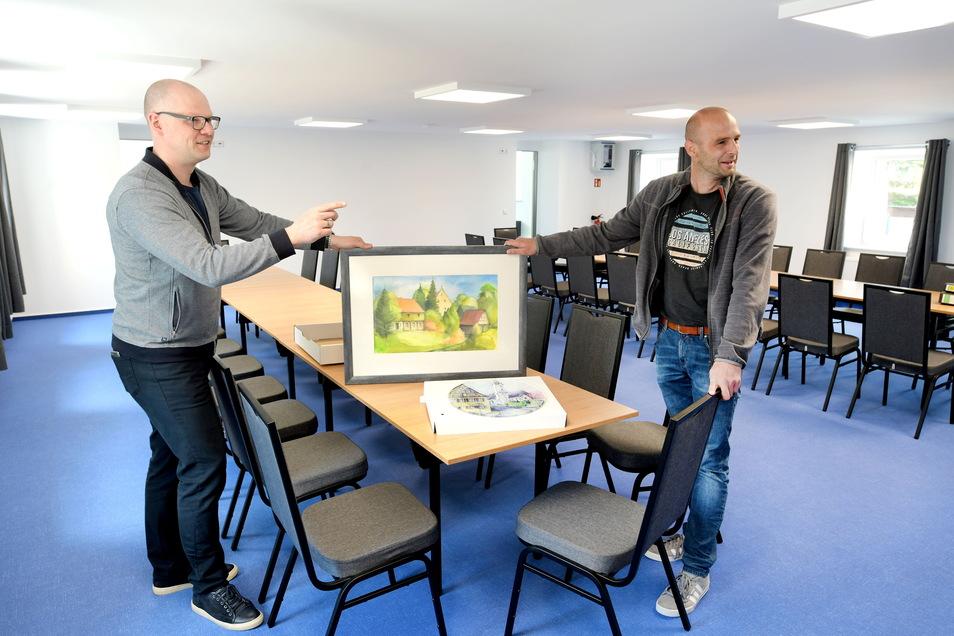 Bürgermeister Markus Hallmann (links) und Bauamtsleiter Michael Erbe suchen im großen Tagungsraum im Obergeschoss einen passenden Platz für eine Mittelherwigsdorfer Ortsansicht des Malers Joachim Hennig.