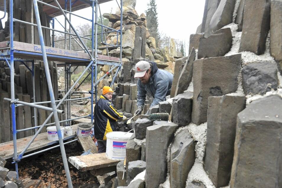 Mitarbeiter der Firma Hoffmann verfugen die Stelengruppe neben der Brücke.