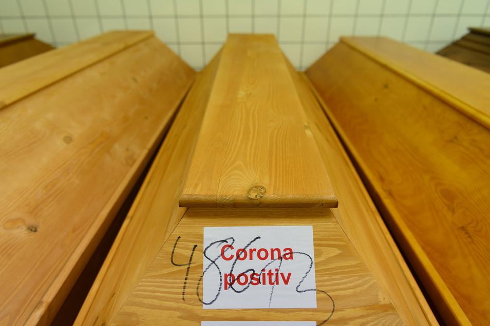 """""""Corona positiv"""" steht auf einem Sarg mit einem Verstorbenen, der an oder mit dem Coronavirus gestorben ist, welcher im Kühlraum des Krematoriums Döbeln steht."""