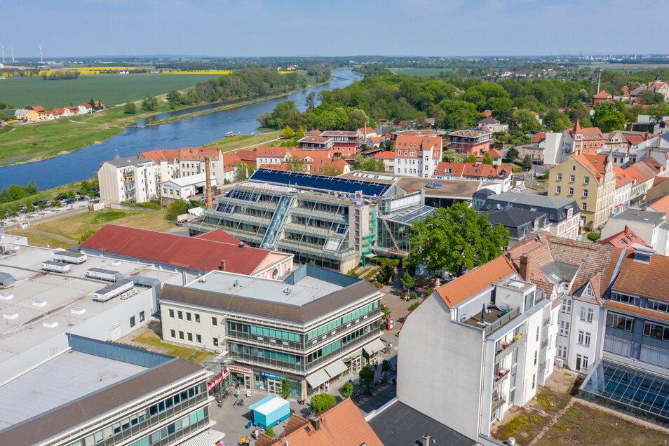 Die Elbgalerie (im Vordergrund) liegt mitten an der Riesaer Hauptstraße. Darüber ist die Zentrale der Sparkasse zu erkennen, oben Elbe und Stadtpark.