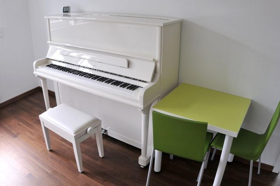 Für die musikalischen Hortkinder steht ein weißes Klavier unter dem Dach zum Üben und Spielen bereit.