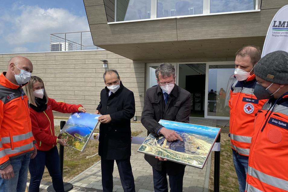 Oberbürgermeister Octavian Ursu (Mitte, links) und Gerd Richter von der LMBV (Mitte, rechts) mit DRK-Mitgliedern vor der neuen Rettungswache.
