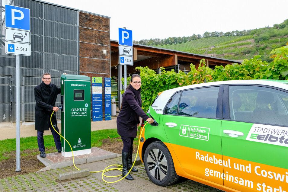 Vicky Jursch von den Stadtwerken Elbtal lädt mit Martin Junge ein E-Fahrzeug an der Stromzapfsäule von Schloss Wackerbarth auf.