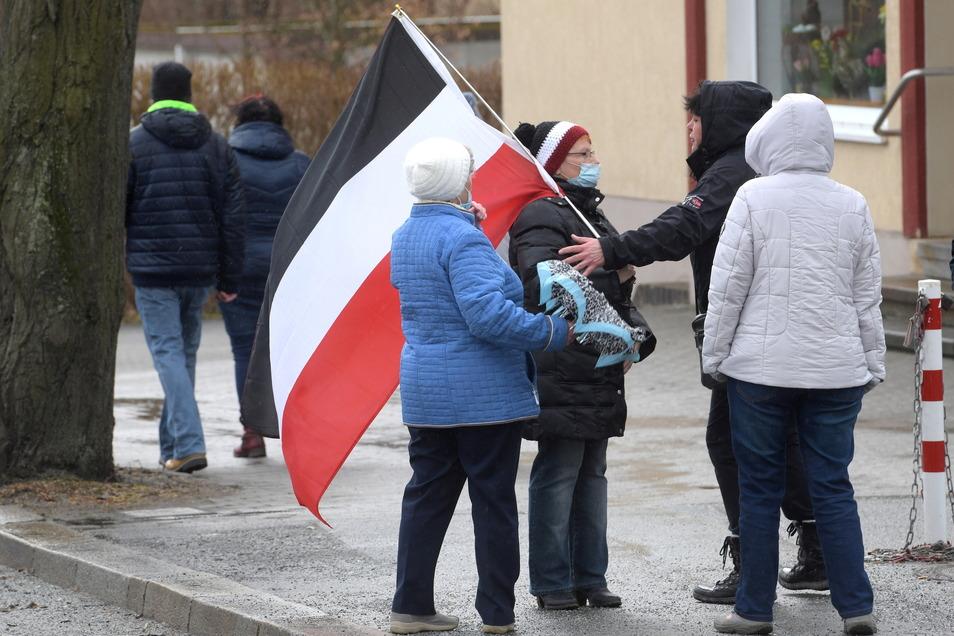 Die Fahne des Deutschen Reiches ist oft zu sehen, vor allem bei den Teilnehmern in Oppach. Polizisten achten darauf, dass die Teilnehmer Masken tragen.