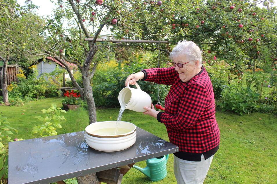 Sabine Posselt füllt die Vogeltränke. Die große Schüssel steht auf einem Tisch, dessen Fuß ein Baumstumpf ist.