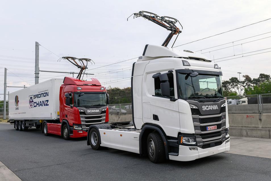 Zwei Scania R450 Hybrid Zugmaschinen mit ausgefahrenem Stromabnehmer stehen vor Beginn der Inbetriebnahme der ersten deutschen Teststrecke für E-Lastwagen mit Oberleitung an einer Raststätte der Autobahn 5 (A5).