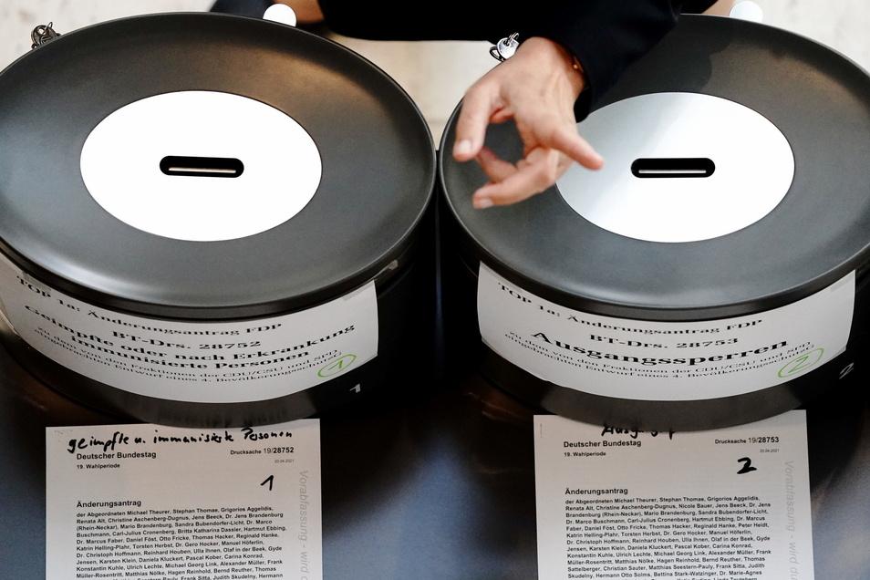 Wahlurnen mit der Aufschrift ·Ausgangssperren· und ·Geimpfte oder nach Erkrankung immunisierte Personen· stehen bei der Abstimmung des Bundestags im Foyer bereit.