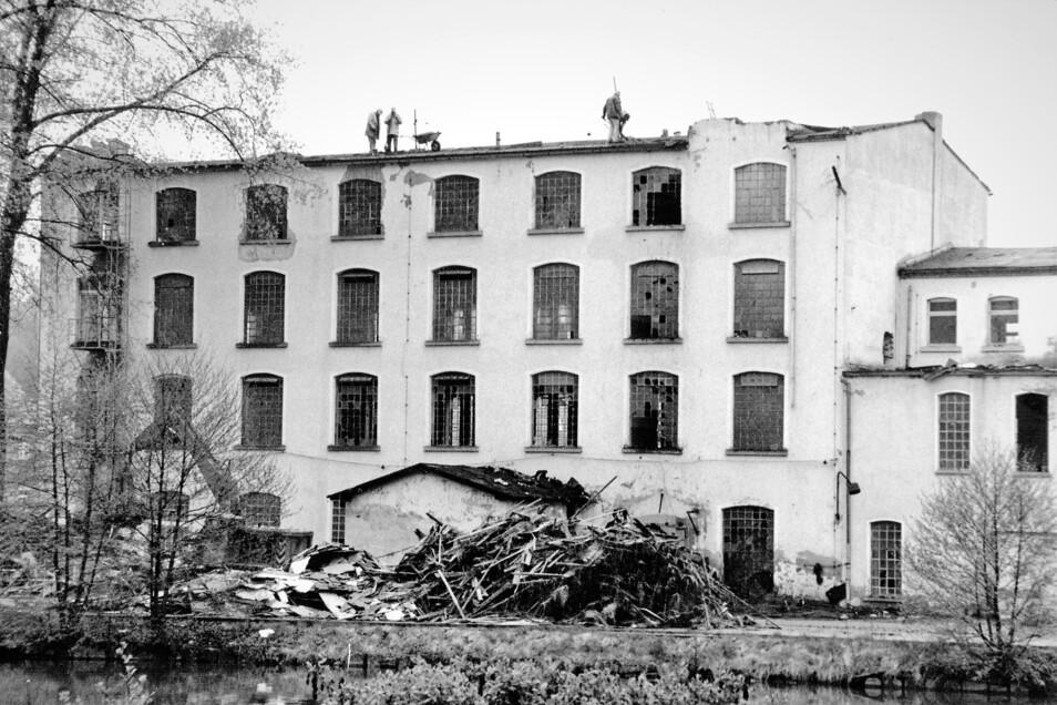"""So wurde vor 25 Jahren die in Oppach """"Frottana"""" genannte Weberei Horn in der Nähe der ehemaligen Tankstelle abgerissen: Arbeiter bauen das Dach zurück, ein Bagger (links unten) nimmt sich bereits erster Gebäudereste an."""