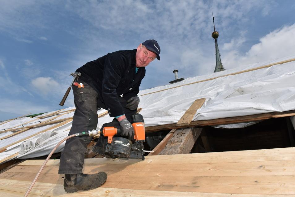 Zimmerer Steffen Finsterbusch bringt die neue Schalung an, damit das Schlossdach wieder solide und regenfest wird.