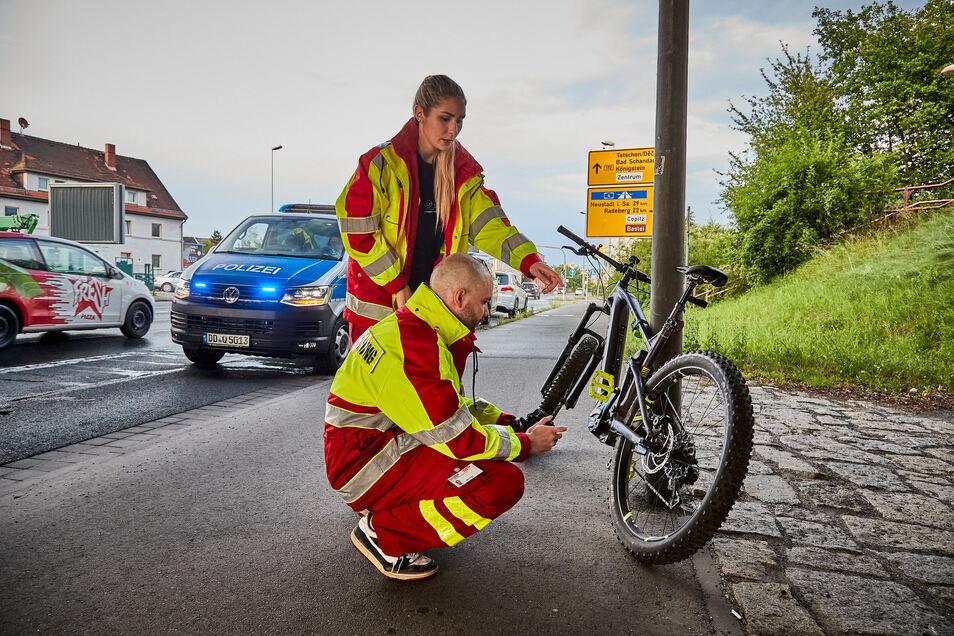 Mitarbeiter der Verkehrsunfallforschung schauen sich das verunglückte Fahrrad an. Der junge Fahrer hat sich schwer verletzt.