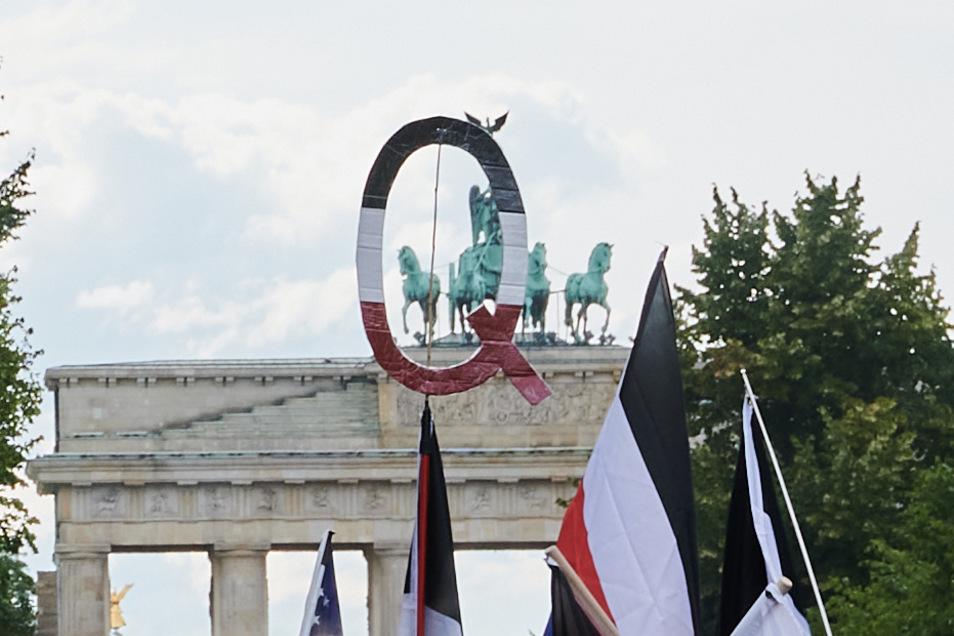 Reichsflaggen und ein Q in den selben Farben halten Demonstranten vor dem Brandenburger Tor. Q steht für QAnon.
