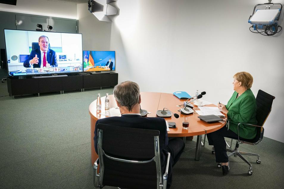 Bundeskanzlerin Angela Merkel (r) und Markus Söder, Ministerpräsident von Bayern und Vorsitzender der Ministerpräsidentenkonferenz, sprechen während einer Videokonferenz mit den Ministerpräsidenten der Länder über Schutzmaßnahmen der Bevölkerung
