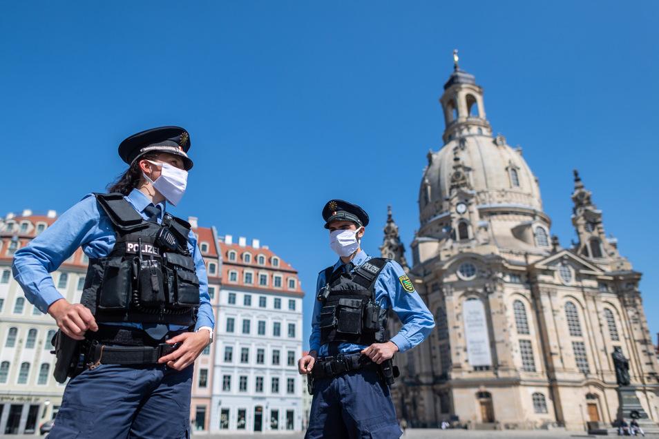Polizisten stehen auf dem Neumarkt vor der Frauenkirche. In der Kirche finden weiterhin keine Gottesdienste statt.