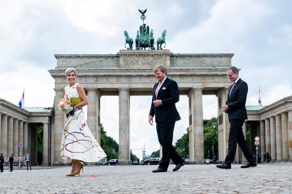 König Willem-Alexander der Niederlande und Königin Maxima gehen zusammen mit Michael Müller (SPD), Regierender Bürgermeister von Berlin, über den Pariser Platz vor dem Brandenburger Tor.