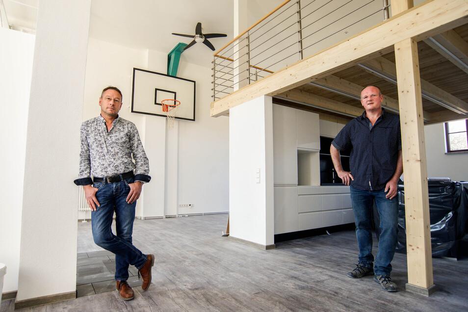 Die Bauherren Andreas Bascha (links) und Edgar Lehmann stehen in einer der neuen Wohnungen, die sie in Neukirch in einer ehemaligen Turnhalle geschaffen haben. Sportgeräte wie der Basketballkorb wurden erhalten.