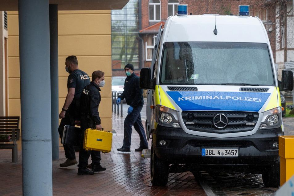 Ein Mitarbeiter der Kriminalpolizei geht mit zwei kleinen Handkoffern auf dem Gelände einer Potsdamer Behinderten-Wohnanlage zu einem Polizeiauto.