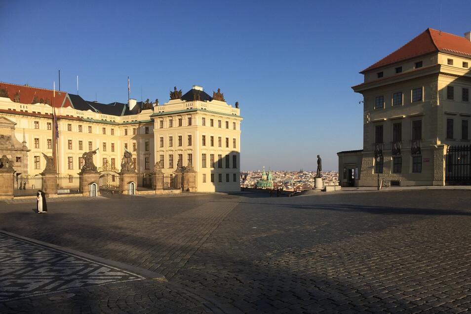 Der Prager Burgplatz, sonst voller Touristen, derzeit menschenleer. Eine Nonne betet vor dem Erzbischöflichen Palais, das wegen eines Covid-19-Falls ebenfalls geschlossen ist. Das Restaurant Kuchyn im Palais Salm rechts hat wegen fehlender Besucher Insolv