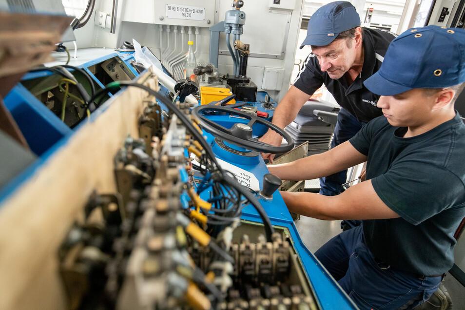 Klaus David (l.), Elektriker in Rente bei der Deutschen Bahn, arbeitet mit Johann Müller, Auszubildender zum Mechatroniker, im Nürnberger Bahnwerk an der Umrüstung im Führerhaus einer Lokomotive.