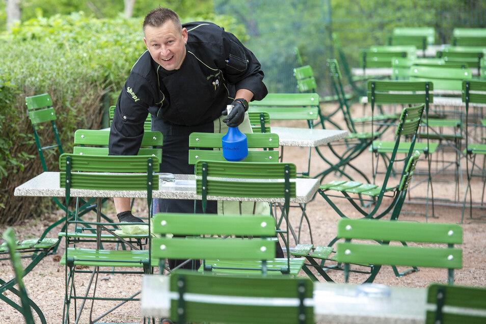 Philipp Skopi desinfiziert im Biergarten die Tische und Stühle, bevor die ersten Gäste kommen.