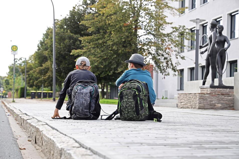 Nachgestellte Szene: Die Abfahrtszeiten der Busse vor der Schule Am Merzdorfer Park passen nicht mehr zum Stundenplan. Für Schüler, die ins Umland müssen, bedeutet das oft lange Wartezeiten.