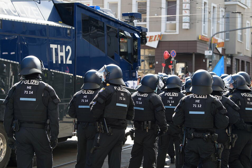 Einsatzkräfte der Polizei stehen in Kassel neben einem Wasserwerfer.